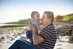 Young father playing with baby son as at the beach Stock Image