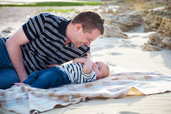 Young father playing with baby son as lying at the beach, Stock Photos