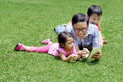 Young father playing with a digital tablet Royalty Free Stock Images