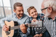 Young father playing guitar while little son and grandfather are royalty free stock images