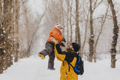 Young father playing with his baby in a snowy park. royalty free stock photo