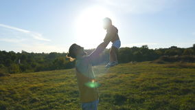 Young father playing with his little son outdoor. Dad lifting up his child at nature. Happy family spending time