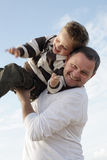 Young father playing with his son. On the beach against sky background Royalty Free Stock Photo
