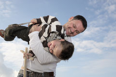 Young father playing with his son. On the beach against sky background Stock Photos