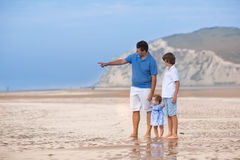 Young father playing with his son and baby daughter on beach Royalty Free Stock Images