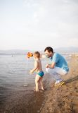 Young father playing with his son at the beach Stock Image
