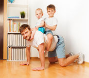 Young father playing with his two sons. Giving them piggy back ride at home Stock Image