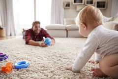 Young father playing with toddler son on the floor at home stock photos