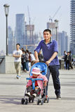 Young father pushes a baby car, Shanghai, China royalty free stock photos