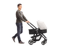 Young father pushing a baby stroller Royalty Free Stock Photos