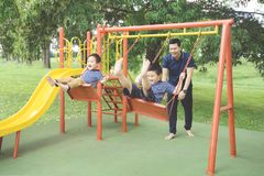 Young father pushing his sons on the swing. Picture of young father pushing his sons on the swing while having fun in the playground Stock Photo