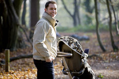 A young father pushing a stroller in the park Stock Photo