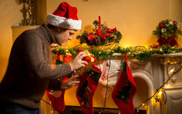 Young father putting gifts in Christmas stockings at fireplace royalty free stock photos