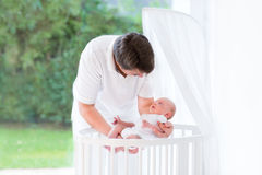 Young father putting his newborn baby into crib Royalty Free Stock Images