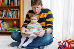 Young father reading book with his cute adorable baby daughter girl. Smiling beautiful child and man sitting together in royalty free stock image