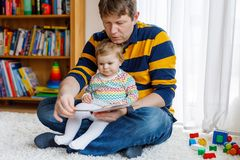 Young father reading book with his cute adorable baby daughter girl stock photos