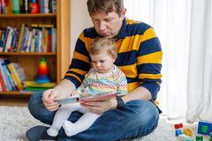 Young father reading book with his cute adorable baby daughter girl. Smiling beautiful child and man sitting together in. Young father reading book with his cute Royalty Free Stock Image