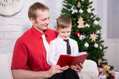 Young father reading book to his son in front of Christmas tree. Happy young father reading book to his son in front of Christmas tree royalty free stock images