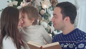 Young father reading Christmas tale, while mother and their happy son whispering secretly royalty free stock photography