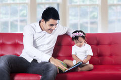 Young father reading story book with his baby Stock Photos