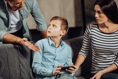 Young father scolding his son for binge-playing. Stop it. Strict young father scolding his son for binge-playing games on the phone while the boy looking at him royalty free stock photos