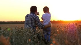 A young father shows a young child the sunset and the sky sitting in a wheat field. The concept of a happy family and