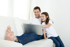 Young father sitting on couch with sweet little daughter using computer laptop Royalty Free Stock Photo