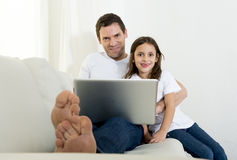 Young father sitting on couch with sweet little daughter using computer laptop Royalty Free Stock Photos