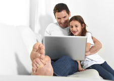 Young father sitting on couch with sweet little daughter using computer smiling happy Royalty Free Stock Images