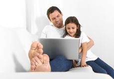 Young father sitting on couch with sweet little daughter using computer smiling happy Stock Photography