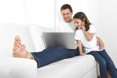 Young father sitting on couch with sweet little daughter using computer smiling happy Royalty Free Stock Photo