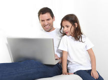 Young father sitting on couch with sweet little daughter using computer smiling happy Royalty Free Stock Photos