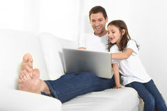 Young father sitting on couch with sweet little daughter using computer smiling happy Stock Photos
