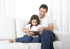 Young father sitting on couch with sweet little daughter using digital tablet smiling happy Stock Photography