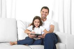 Young father sitting on couch with sweet little daughter using digital tablet smiling happy Royalty Free Stock Image