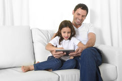 Young father sitting on couch with sweet little daughter using digital tablet smiling happy Royalty Free Stock Images