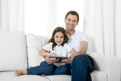 Young father sitting on couch with sweet little daughter using digital tablet smiling happy Stock Photos
