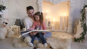 Young father sitting with daughter at fireplace and telling story on Christmas eve stock video