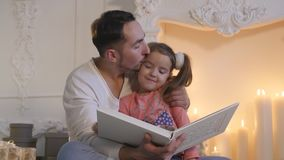 Young father sitting with daughter at fireplace and telling story on Christmas eve stock video footage