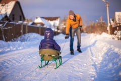 Young father sledding his little daughter on a Stock Images