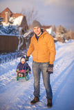 Young father sledding his little daughter on a Royalty Free Stock Photos