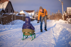Young father sledding his little daughter on a Royalty Free Stock Images