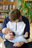 Young father with sleeping baby son on arm Stock Photography