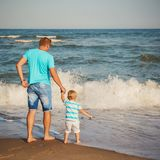Young father with small son walking at beach together near the ocean, happy lifestyle family concept. Back view.  Royalty Free Stock Photo
