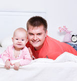 Young father with smiling baby lying Stock Photos