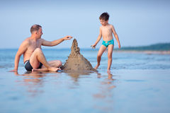 Young father and son building sand castle at beach Stock Photos