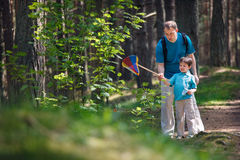Young father and son catching butterfly in forest Royalty Free Stock Photo