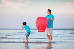 Young father and son flying fire lantern together Royalty Free Stock Images