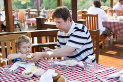 Young father and son having breakfast together in summer Royalty Free Stock Image