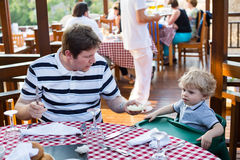 Young father and son having breakfast together in summer Royalty Free Stock Photo
